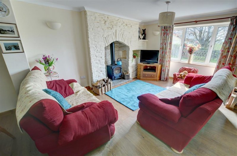 The charming sitting room has a woodburner in the stone fireplace and is furnished with big comfy sofas