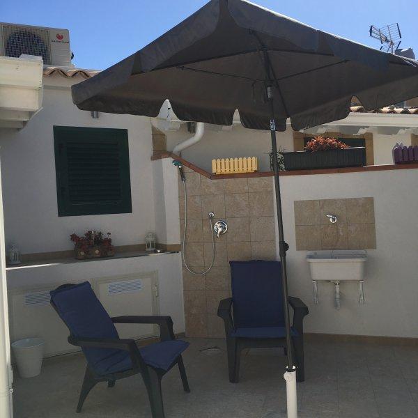 solarium avec salon - jardin, douche extérieure et d'un lavabo.