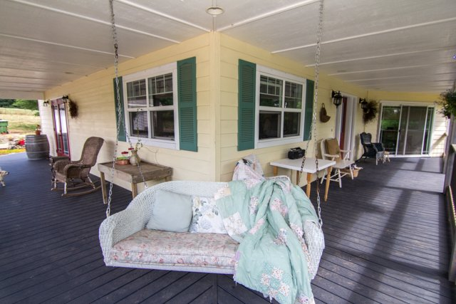 Large wraparound porch with vineyard and mountain views, sun room and swing~ perfect for sunsets