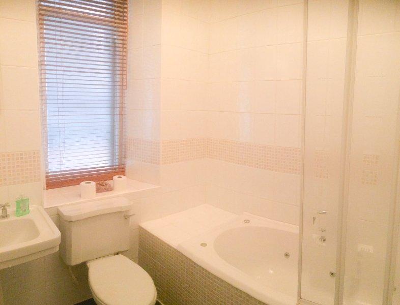 2 Badezimmer mit WC, Waschbecken und Jacuzzi-Bad mit Dusche über die Badewanne