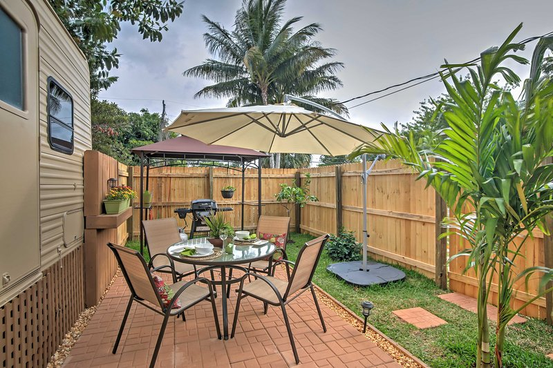 Swaying palms, an outdoor patio and a shaded grilling space welcome you to your private fenced yard, adorned with thriving potted plants!