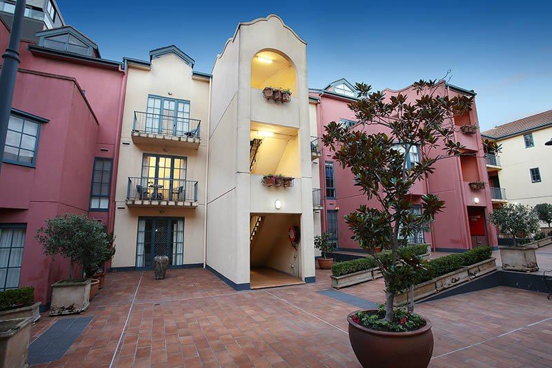 St Kilda serviced apartment bedroom (with light on) from Tuscan courtyard of pots, plants & vines