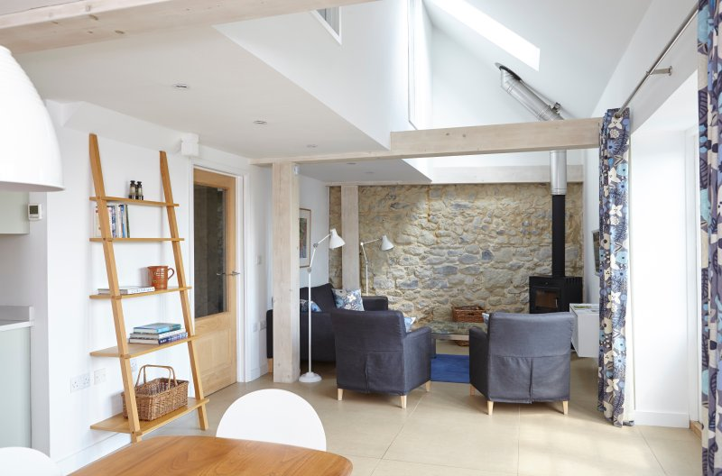 Open plan living room in the Barn with a 400 year old stone wall. Wood burner for the winter months.