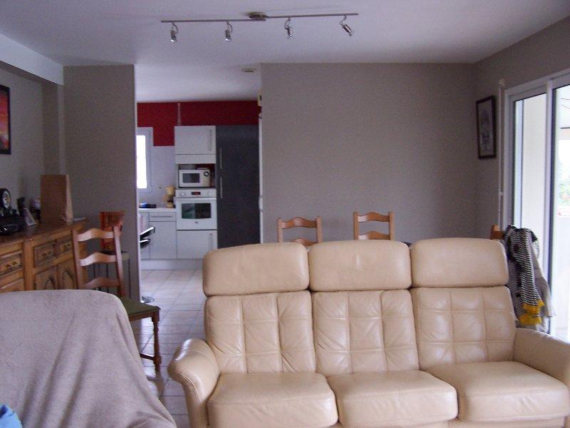 Sofá da sala com vista para a sala de jantar e cozinha