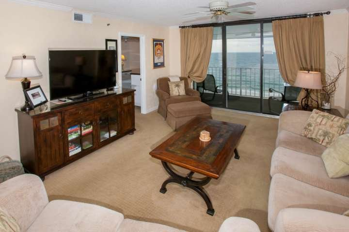 Woonkamer met zitplaatsen voor 6 personen met uitzicht op de Golf front balkon
