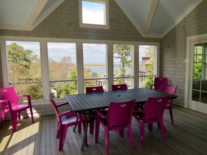 The spacious covered screened porch has outdoor dining and also great views