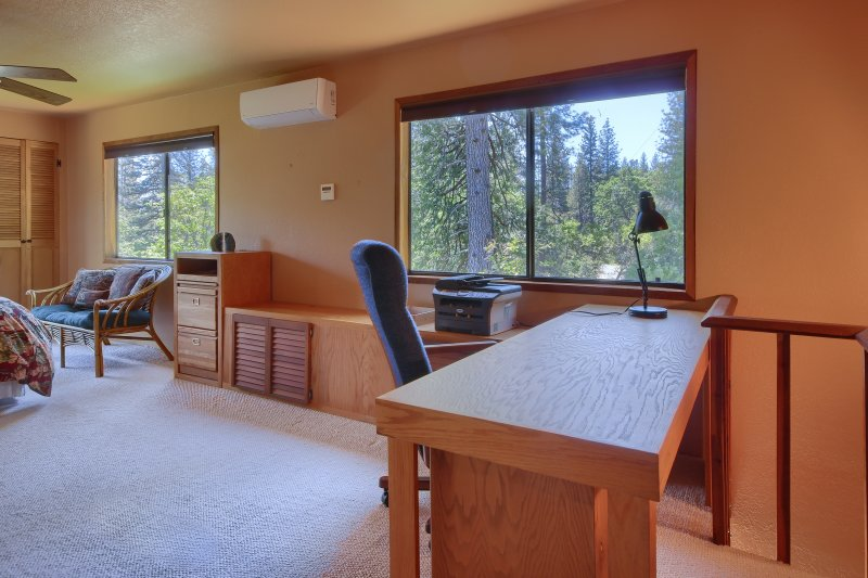 Loft bedroom with desk and tree-top views