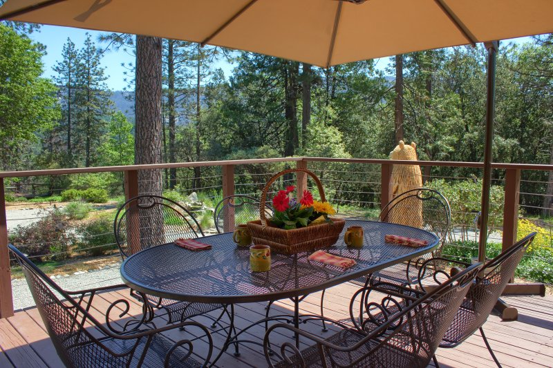 Dining area on wrap-around deck has lovely views of gardens, fountain, and mountains