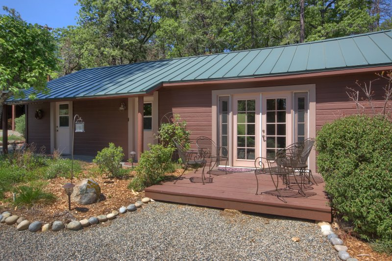 French doors of cottage open to small deck