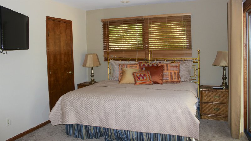 The master bedroom has a king bed. There is a large wall mounted HDTV.