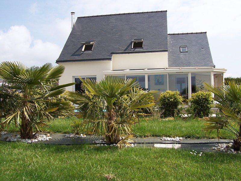 Frente da casa com varanda e área de grande gramado com palmeiras