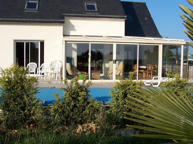 Frente da casa com varanda, piscina e área de grande gramado com palmeiras