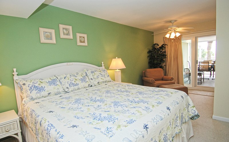 The master bedroom has a king size bed, sitting area, en suite full bathroom and sliding glass doors out to the deck with oceanview.