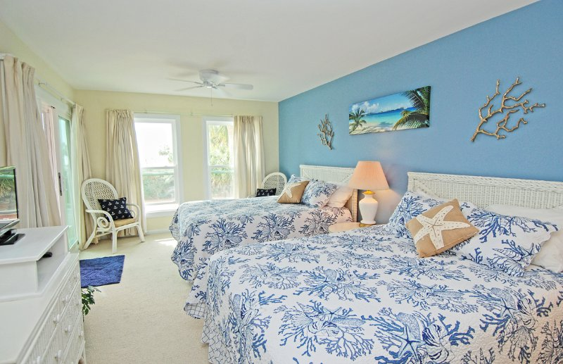 The 2nd bedroom has two queen beds, flat screen TV, sliding glass doors out to the deck and an en suite bathroom.