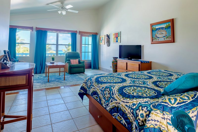 Upstairs front bedroom with king bed, sitting area, & private veranda/balcony