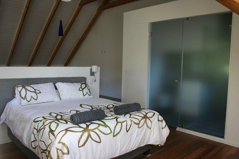 Queen bed with bathroom behind glass doors