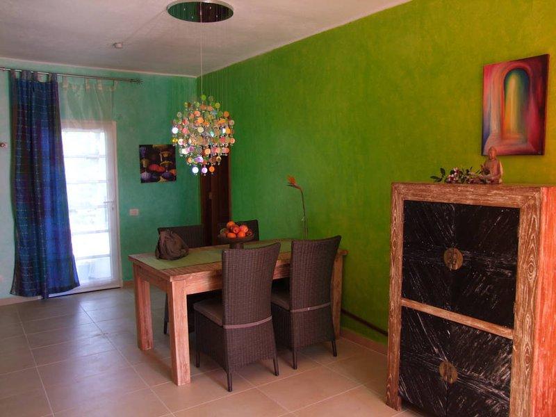 Entrada mesa porta de jantar e em primeiro plano é um gabinete de casamento balinês, com TV
