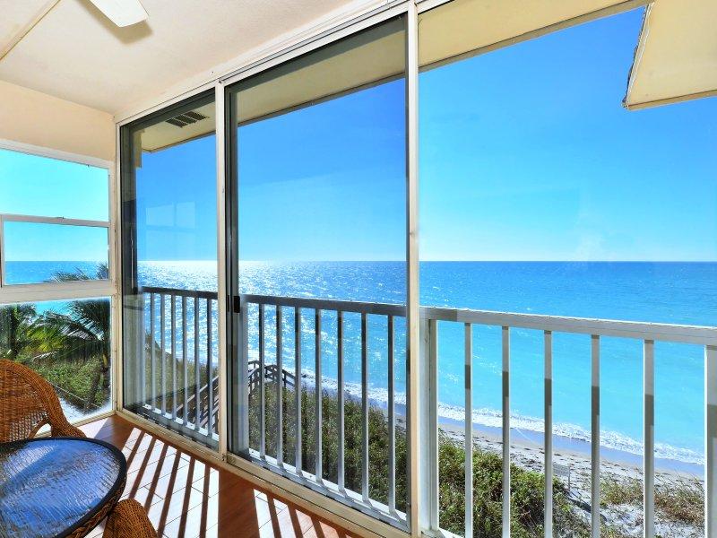 Cerrado, lanai con aire acondicionado tiene una vista increíble del Golfo y la playa a continuación - mesa de comedor se coloca en la terraza para disfrutar mejor de las vistas espectaculares.