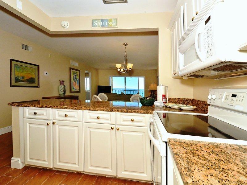 Cocina moderna, completamente renovada con encimeras de granito, salpicaduras de azulejos de vidrio, se abre a la sala de estar / comedor y ventana / puerta con vista a la bahía y muelles