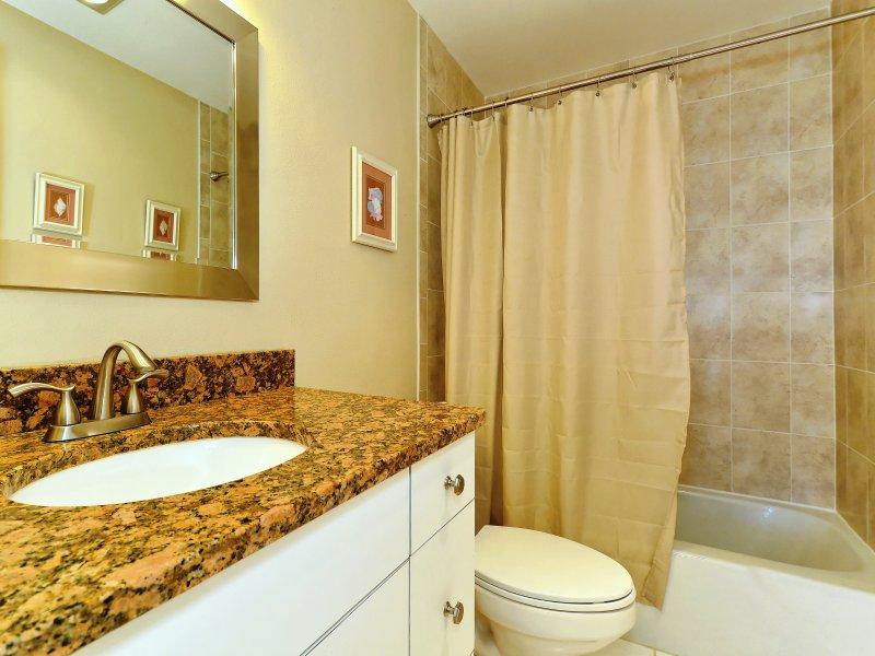 Baño principal con encimera de granito, pisos de baldosas y combinación de azulejo y bañera