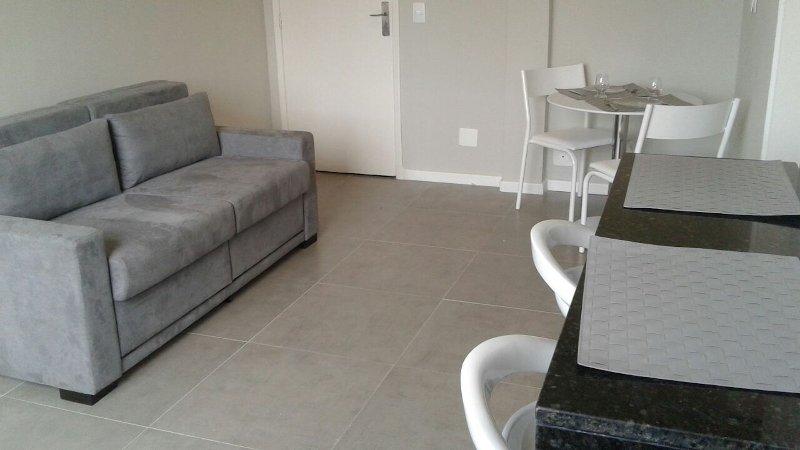 Wohnzimmer mit Schlafcouch, Tisch, Stühle, Theke mit Hockern