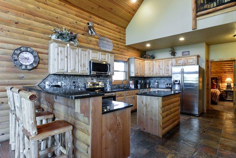 Cocina completamente equipada con encimeras de granito sólido y electrodomésticos de acero inoxidable.