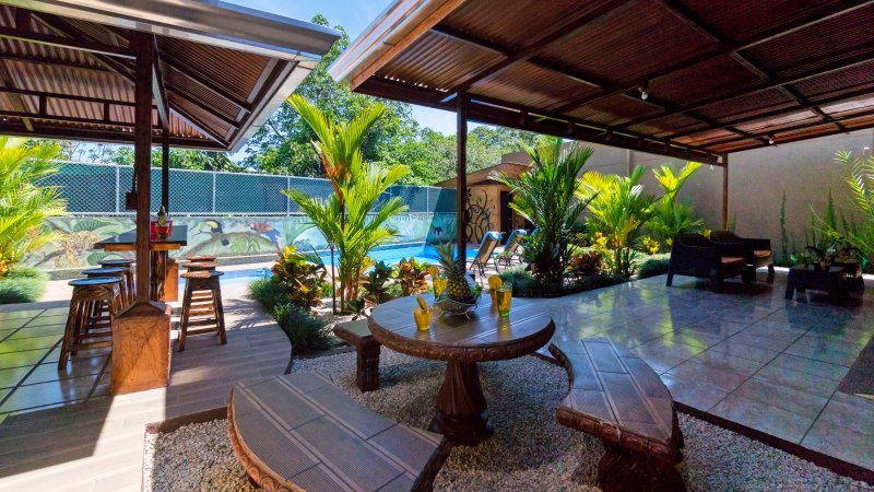 Dining area with bar island to the left and view of the pool.