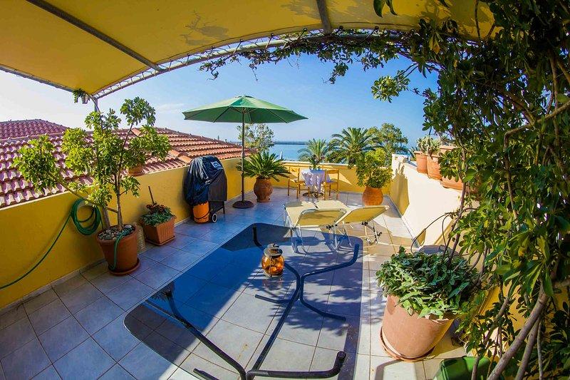 Zonnige noorden balkon met uitzicht op de Venetiaanse vuurtoren, de jachthaven en de belangrijkste Rethymno strand.