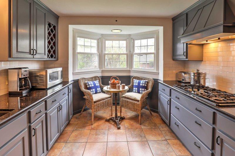 Cette cuisine est équipée d'armoires foncées et tous les appareils noirs pour une sensation élégante.