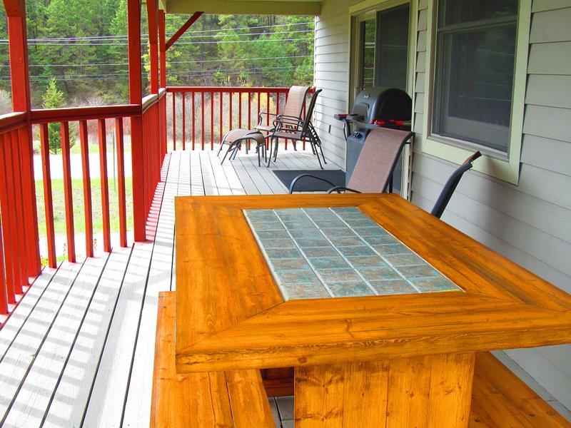 terraza exterior cubierta con mesa de picnic, parrilla de barbacoa y asientos