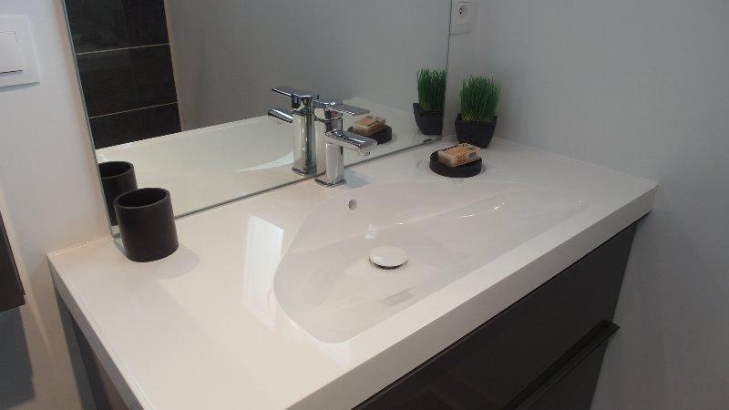 Grand lavabo avec 2 grands tiroirs contenant des serviettes de bain, sèche, savons et shampoings
