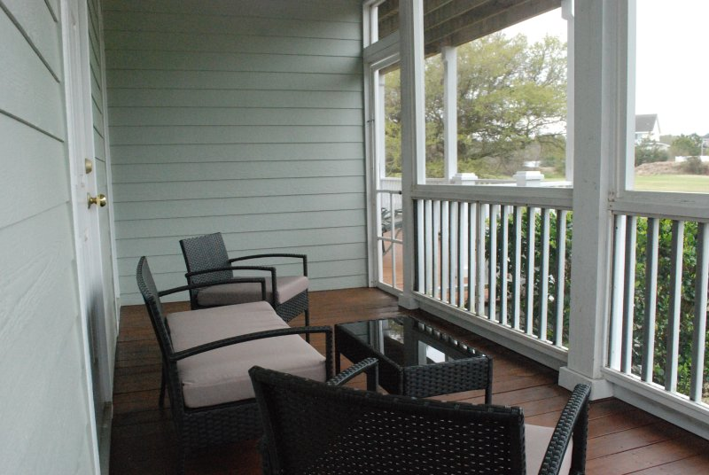 Screened in porch with a beautiful view of the 13th fairway.