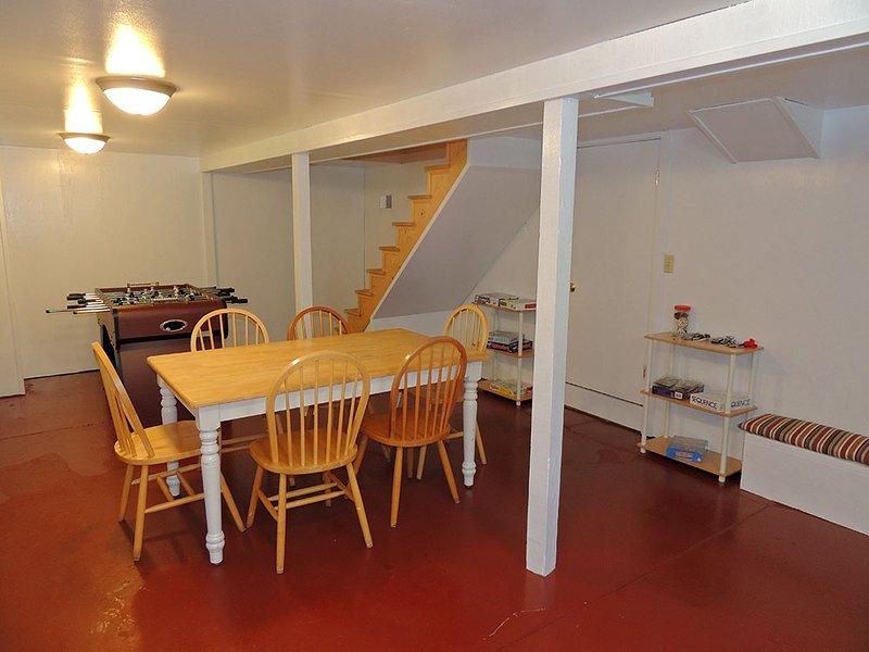 Beneden recreatieruimte met bordspellen, tafelvoetbal tafel en een dartbord.