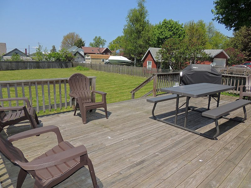 Grote achtertuin dek met picknicktafel, gas grill en Adirondack stoelen.