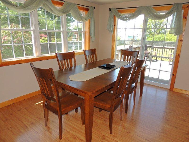 Eetkamer tafel met zitplaatsen voor 6 glazen schuifdeuren openen naar een groot terras en een eigen tuin.