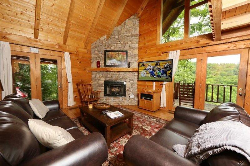 Mysigt vardagsrum med stor platt-TV och gas spis