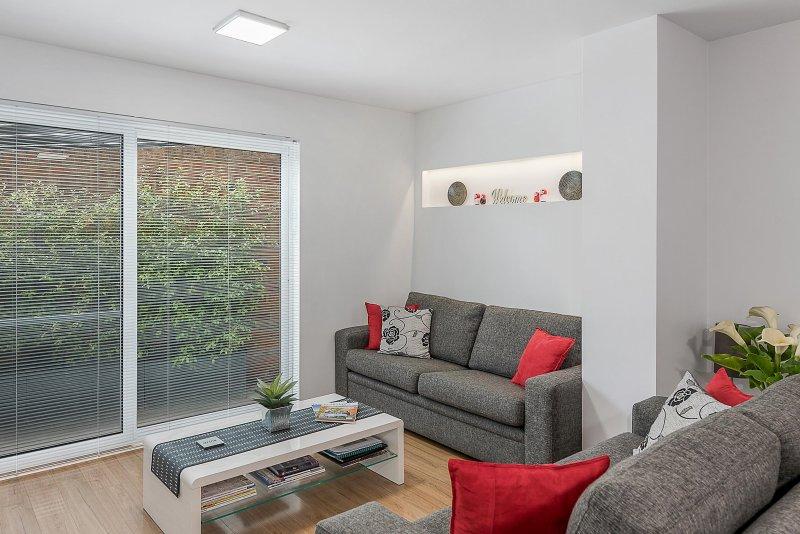Relajante zona de salón con puertas correderas de cristal que se abre a un pequeño patio.