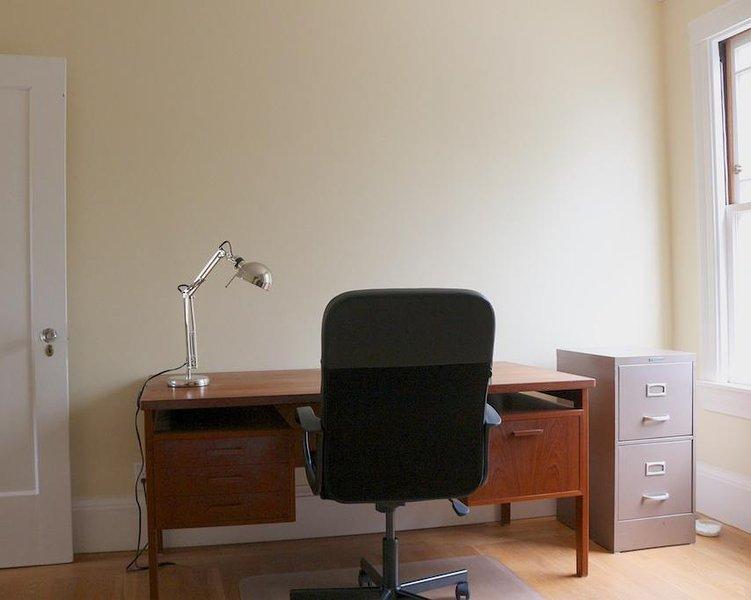 Grote vintage teak bureau met een bestand lade
