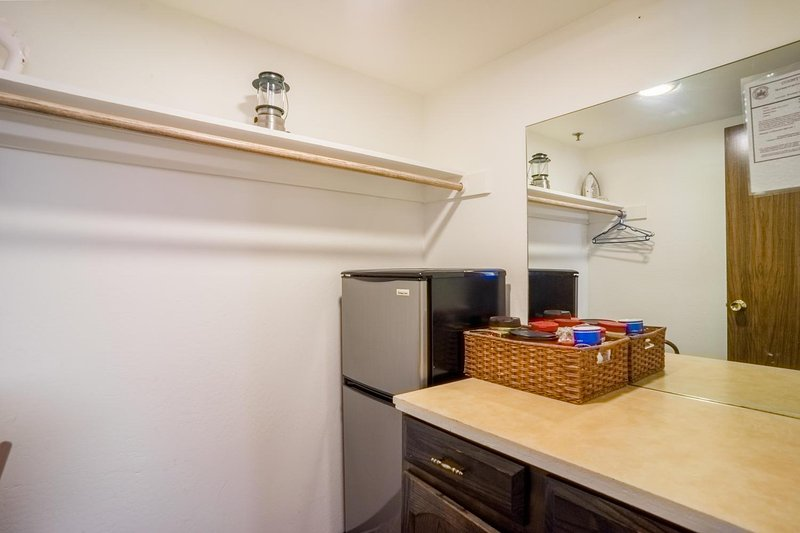Walk in closet behind kitchen with 2nd refrigerator.