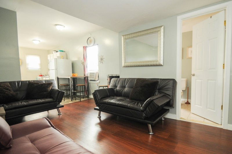 Great living room area with 3 sofas, TV, AC, and a nice comfortable setting for gatherings