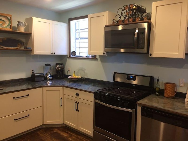 Big open kitchen with gas stove and dishwasher.