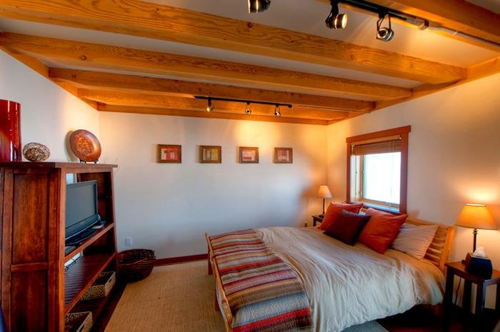 The cozy bedroom has a queen sized bed and a timbered ceiling.
