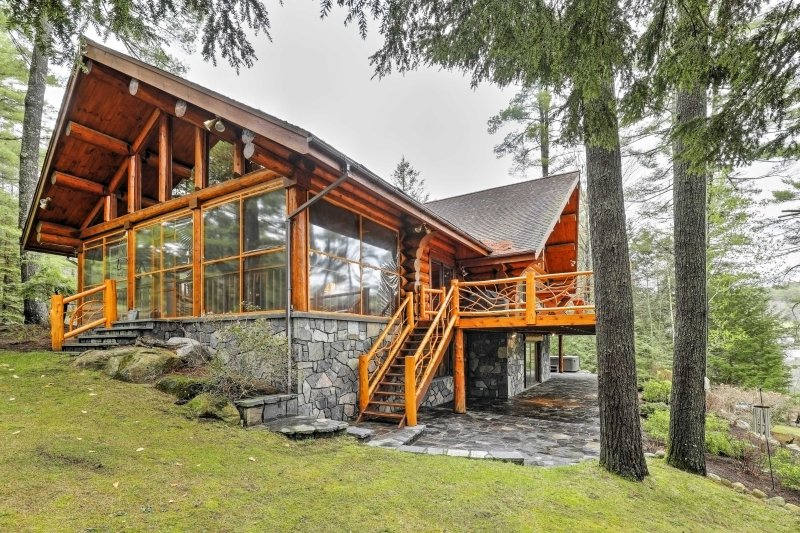 Escape to this Upstate New York vacation rental cabin and enjoy scenic views overlooking the private lakefront!