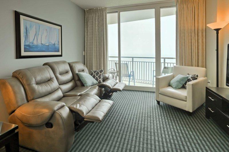 Entspannen Sie sich im Wohnzimmer auf dem luxuriösen Ledersessel Sofa und besuchen Sie mit Ihren Mitreisenden, wie Sie auf den herrlichen Blick auf das Meer von den Glasschiebetüren blicken.