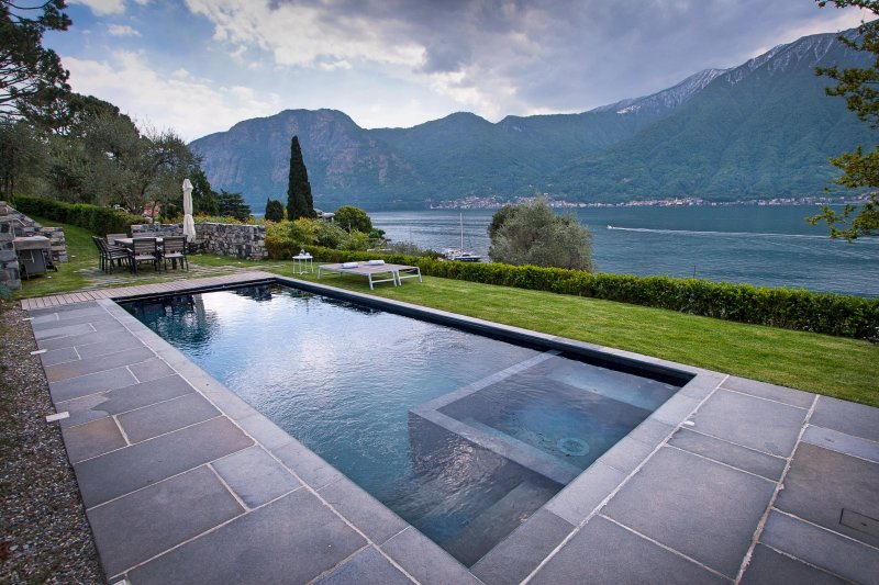piscina climatizada con vista al lago y un spa y zona de barbacoa.