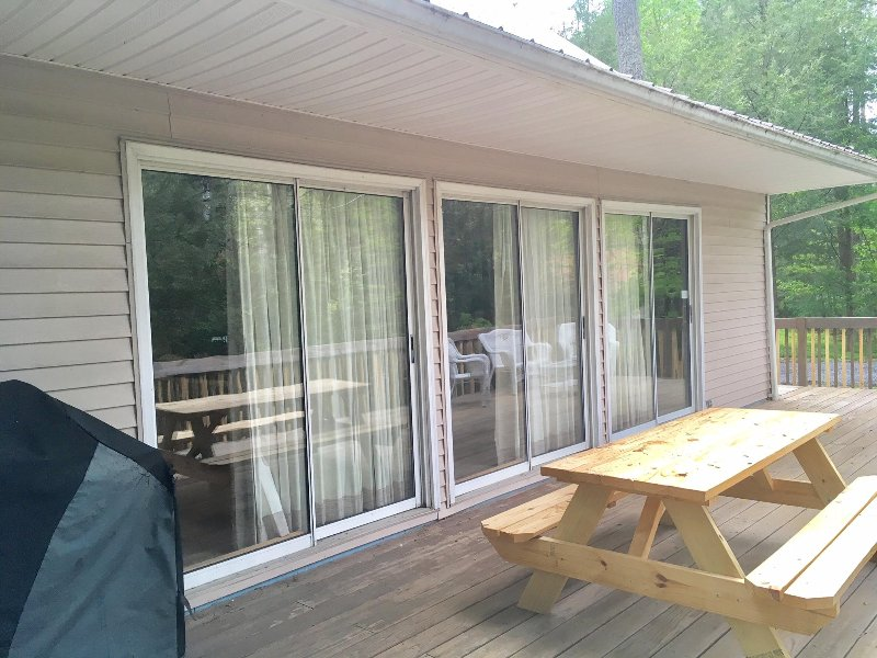 Large deck with table, grill and seating. Private wooded lot.