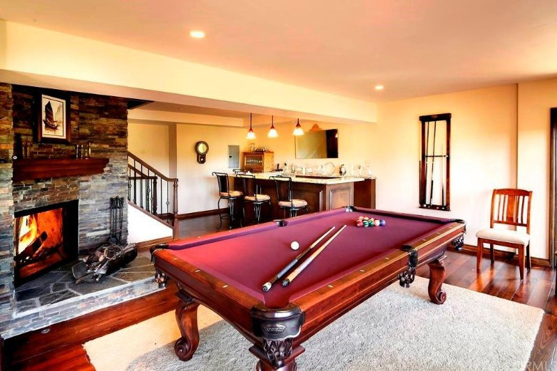 Game room with bar, fireplace and pool table.