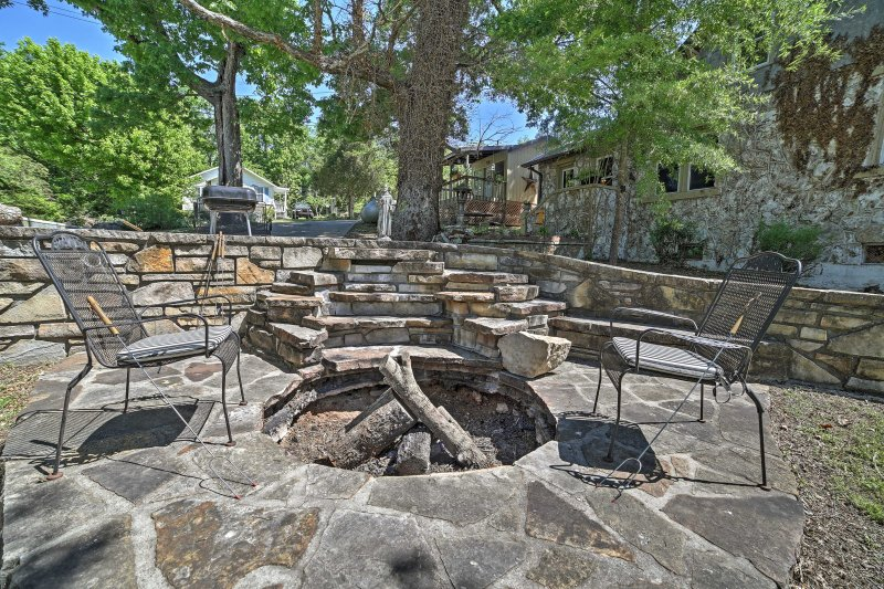 The property boasts a lush yard and several outdoor seating options, along with an in-ground fire pit.