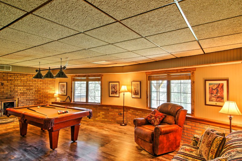The lower floor has a rec room that features a pool table, a small foosball table, a 55-inch flat-screen Smart TV and a dart board for your entertainment.