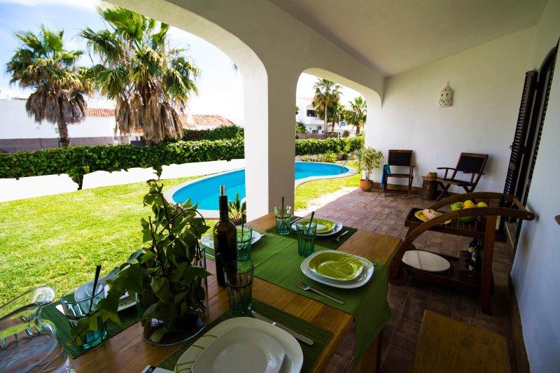 terrasse couverte orientée plein sud et à la piscine, avec table à manger pour 8 personnes